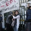 Former employees of the Greek state television ERT comfort each other outside its headquarters at Agia Paraskevi suburb north of Athens