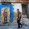 A+man+walks+past+an+abandoned+building+covered+with+graffiti+in+Athens