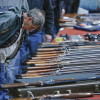 FILE - In this Jan. 26, 2013 file photo, a customer looks over shotguns on display at the annual New York State Arms Collectors Association Albany Gun Show at the Empire State Plaza Convention Center in Albany, N.Y. After struggling to sway both state and federal lawmakers, proponents of expanding background checks for gun sales are now exploring whether they will have more success by taking the issue directly to voters. While advocates generally prefer that new gun laws be passed through the legislative process, especially at the national level, they are also concerned about how much sway the National Rifle Association has with lawmakers. Washington state Rep. Jamie Pedersen, a Democrat who had sponsored unsuccessful legislation on background checks at the state level, said a winning ballot initiative would make a statement with broad implications. (AP Photo/Philip Kamrass, File)