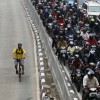A man rides a bicycle in a bus lane next to a morning rush hour traffic jam in Jakarta November 10, 2011. Indonesia's central bank said on Thursday it saw economic growth in 2012 could slow to below 6.5 percent, as it cut its benchmark overnight interest rate by a surprise 50 basis points to a record low 6 percent to ward off the effect of a slowdown in Europe and China. REUTERS/Supri  (INDONESIA - Tags: BUSINESS SOCIETY TPX IMAGES OF THE DAY TRANSPORT)