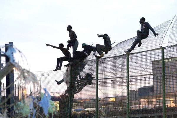 epa04144082 Sub-Saharan immigrants, who tried to cross into Spanish territory, shout slogans like 'Spain, Spain' or 'Freedom' on top of a fence at the Spanish-Moroccan border in Melilla, Spanish autonomous city in northern Africa, early morning 28 March 2014. Several hundred sub-Saharan irregular immigrants tried to reach Spain in several attempts. EPA/F.G. GUERRERO BEST QUALITY AVAILABLE