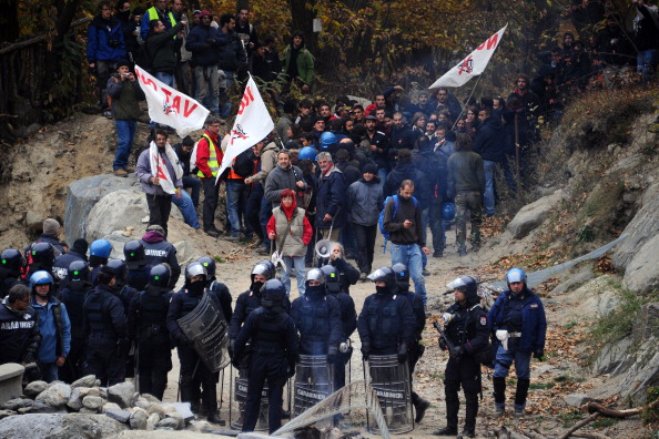 "Demonstrators of the ""No Tav"" (No to High-Speed Trains) movement are stopped by police forces on October 23th, 2011, in Chiomonte, during a protest against a high-speed train line between Lyon and Turin, near the village of Baita Clarea in the Alpine region of Val di Susa on October 23, 2011. The protest organised by the No Tav (No to High-Speed Trains) movement and residents of the Susa Valley have fiercely opposed the plan, saying the construction of tunnels would damage the environment. France and Italy signed a deal in 2001 on building a line through the area, a strategic link in the European network that would cut travel time between Milan and Paris from seven to four hours. AFP PHOTO/ OLIVIER MORIN (Photo credit should read OLIVIER MORIN/AFP/Getty Images)"