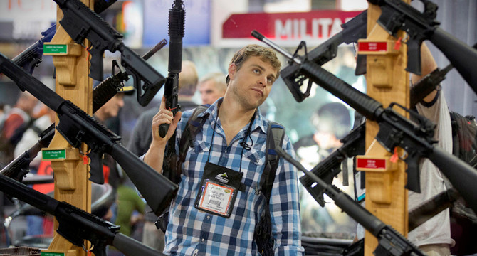 Michael Kiefer, of DeFuniak Springs, Fla., checks out a display of rifles at the Rock River Arms booth during the 35th annual SHOT Show, Thursday, Jan. 17, 2013, in Las Vegas. The world's largest gun and outdoor trade show runs through Friday. (AP Photo/Julie Jacobson)