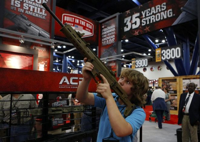 WCENTER 0XNFAEAJGD epa03686671 James Beaver, 13, looks through the scope of a Bushmaster gun during the 2013 National Rifle Association (NRA) Annual Meetings & Exhibits at the George R. Brown Convention Center in Houston, Texas, USA, 03 May 2013. The National Rifle Association is a nonprofit organization that promotes firearm ownership, as well as police training, firearm safety, marksmanship, hunting and self-defense training in the United States. The association has over four million members. EPA/AARON M. SPRECHER