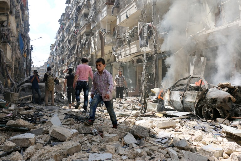 People walk amid the rubble of destroyed buildings following a reported air strike on the rebel-held neighbourhood of al-Kalasa in the northern Syrian city of Aleppo, on April 28, 2016. The death toll from an upsurge of fighting in Syria's second city Aleppo rose despite a plea by the UN envoy for the warring sides to respect a February ceasefire. / AFP PHOTO / AMEER ALHALBI