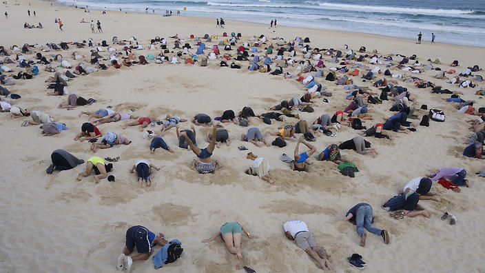 A supplied image obtained Thursday, November 13, 2014 of protesters' heads in the sand, on Bondi Beach, Sydney, Thursday, November 13, 2014. Protesters buried their heads in the sand at Bondi beach to highlight the Prime Minister Tony Abbott's refusal to include climate change in the G20 agenda. (AAP Image/350.org Australia, Tim Cole) NO ARCHIVING, EDITORIAL USE ONLY