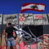 A Lebanese activist paints graffiti on a concrete wall installed by authorities near the main Lebanese government building, in downtown Beirut, Lebanon, Tuesday, Aug. 25, 2015. Anticipating more protests, authorities installed a concrete wall near the main Lebanese government building, site of the largest protests. On Saturday and Sunday nights, police fired tear gas and water cannons at the protesters, battling them in the streets of Beirut in dramatic clashes, wounding dozens. (AP Photo/Hassan Ammar)