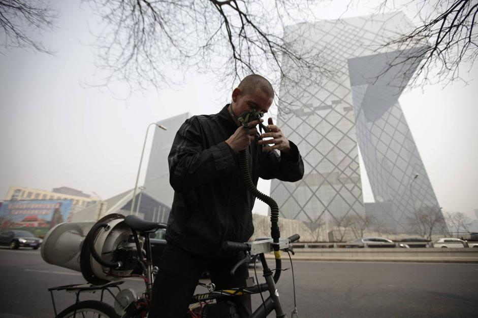 "Artist Matt Hope adjusts the helmet linked to his air filtration bike in front of the China Central Television (CCTV) building on a hazy day in Beijing, March 26, 2013. Using an IKEA perforated garbage can, moped helmet, fighter-pilot breathing mask, wheel-powered generator and home air filtration system, Beijing-based artist Matt Hope built a ""breathing bicycle"" as a way of protecting himself from air pollution. While pedalling, electricity is generated for the power to activate the system to filter out haze and provide the rider with clean air, local media reported. According to the U.S. embassy monitor, the air quality today is classified as ""very unhealthy"". REUTERS/Petar Kujundzic (CHINA - Tags: ENVIRONMENT SOCIETY POLITICS)"